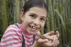Girl Holding Frog Outdoors - stock photo