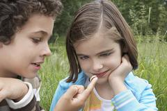 Siblings Watching Caterpillar Outdoors - stock photo