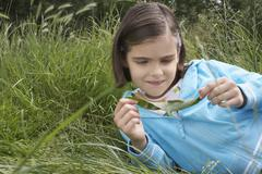 Girl Examining Caterpillar On Leaf Stock Photos