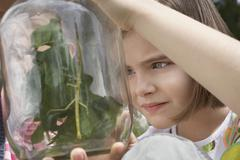 Girls Examining Stick Insects In Jar - stock photo