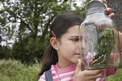 Girl Examining Stick Insects In Jar - stock photo