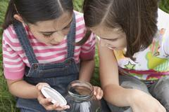 Stock Photo of Girls Looking Into Jar