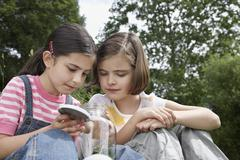 Girls Looking Into Jar Of Insects Outdoors - stock photo