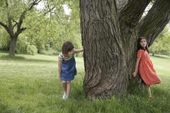 Girls Playing Hide And Seek By Tree - stock photo