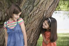 Girls Playing Hide And Seek By Tree Stock Photos