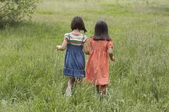 Girls Walking Together In Grassy Field - stock photo