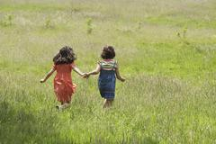 Girls Walking Together In Grassy Field Stock Photos