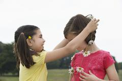 Girl Giving Friend Daisy Chain Stock Photos