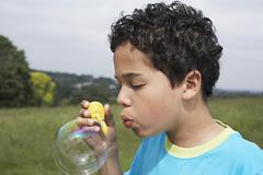 Boy Blowing Soap Bubble In Field - stock photo