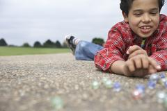 Stock Photo of Boy Playing Marbles On Playground