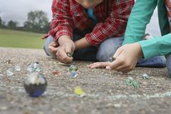 Siblings Playing Marbles On Playground - stock photo