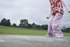 Girl Playing Hop-Scotch In Playground Stock Photos