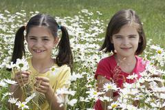 Stock Photo of Girls Among Flowers In Meadow