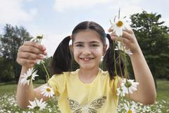 Girl Holding Daisy Chains In Meadow Stock Photos