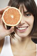 Happy Woman With Half Grapefruit In Front Of Face Stock Photos