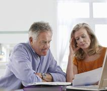 Worried Mature Couple With Bills At Dining Table Stock Photos