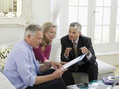 Stock Photo of Couple With Financial Advisor At Sofa