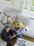 Stock Photo of Woman With Financial Advisor On Sofa