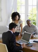 Couple With Financial Advisor At Table - stock photo