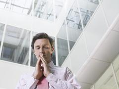 Businessman With Hands Clasped In Office Atrium - stock photo