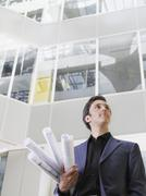 Businessman With Blueprints In Office Stock Photos