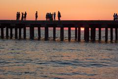 people on the old sea pier at sunset - stock photo