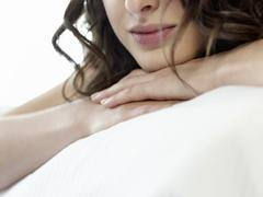 Closeup Of Woman Resting Head On Clasped Hands - stock photo
