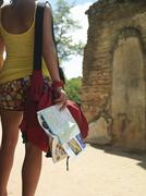 Woman By Ancient Ruins With Guidebook - stock photo
