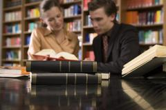 Blurred Couple At Library Desk With Focus On Books - stock photo