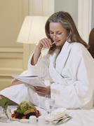 Stock Photo of Woman In Bathrobe Reading Documents In Bed
