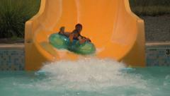 Person on Tube Water Slide Splashing Into Pool Stock Footage