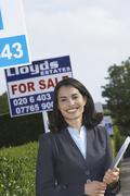 Real Estate Agent By For Sale Sign Outside House - stock photo