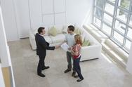 Stock Photo of Real Estate Agent Shaking Hands With Man By Woman In New Home