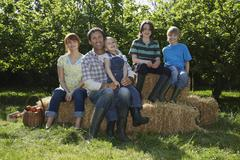 Family Sitting On Hay Bales Near Orchard - stock photo