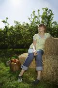 Stock Photo of Thoughtful Woman Sitting On Hay Bales Near Orchard
