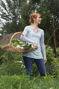 Cheerful Woman With Vegetable Basket In Garden - stock photo