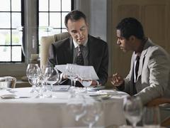 Businessmen Analyzing Documents At Restaurant Table Stock Photos