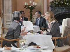 Two Businesswomen Looking At Documents At Restaurant Table Stock Photos