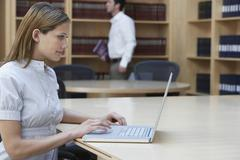 Office Worker Using Laptop In Office Stock Photos