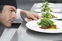 Male Chef Preparing Salad In Kitchen Stock Photos