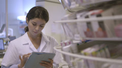 MS Female pharmacist searching medicine in pharmacy with digital tablet Stock Footage