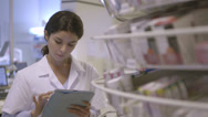 Stock Video Footage of MS Female pharmacist searching medicine in pharmacy with digital tablet