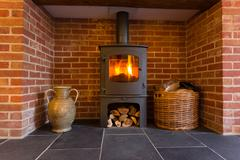 wood burning stove in brick fireplace - stock photo