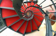 Stock Photo of spiral staircase with red carpet for a dizzying ascent