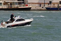 Ship of law enforcement with a carabienire on patrol in venice Stock Photos