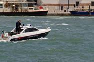 Stock Photo of ship of law enforcement with a carabienire on patrol in venice