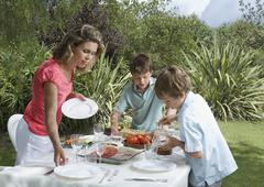 Mother And Sons Setting Dinner Table Outdoors Stock Photos