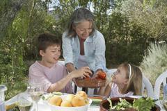 Senior Woman Serving Fruit To Kids - stock photo
