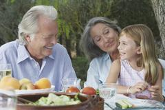 Grandparents With Granddaughter At Outdoor Table Stock Photos