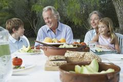 Grandparents With Grandchildren At Outdoor Table Stock Photos
